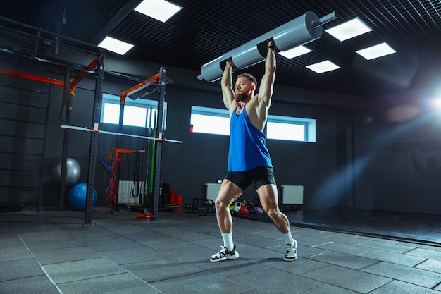 野生のエネルギー。若い筋肉質の白人アスリートは、ジムでトレーニングを行い、筋力トレーニングを行い、練習し、ウェイトやバーベルを使って上半身を鍛えます。フィットネス、健康、健康的なライフ スタイルのコンセプト。