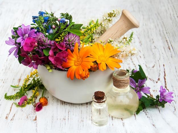 Дикий цветок и листья травы в ступке