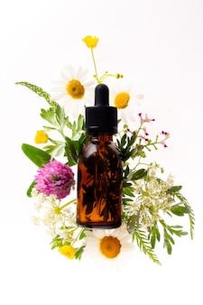 野生の花と白の薬のガラス瓶