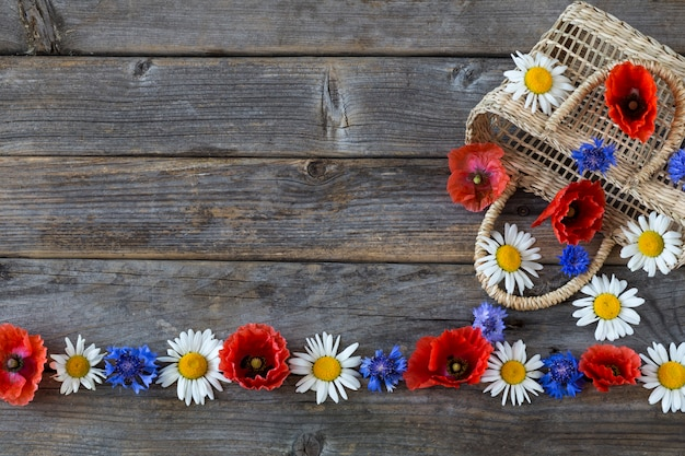 The wild flowers are poured out of the basket: poppies, chamomile and cornflowers