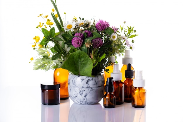 大理石の乳鉢と薬のガラス瓶の中の野生の花、エッセンシャルオイル、化粧品オイル、アロマセラピー、植物療法、代替医療、自然なスキンケア。