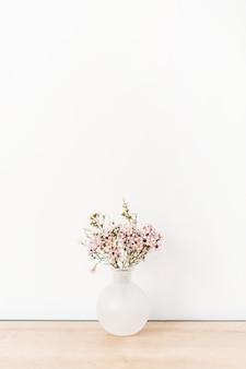 白い壁の前に野の花。最小限の構成