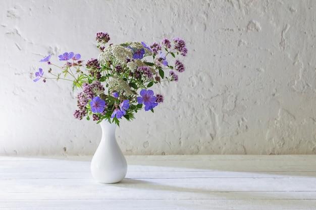 Полевые цветы в белой вазе на белом фоне