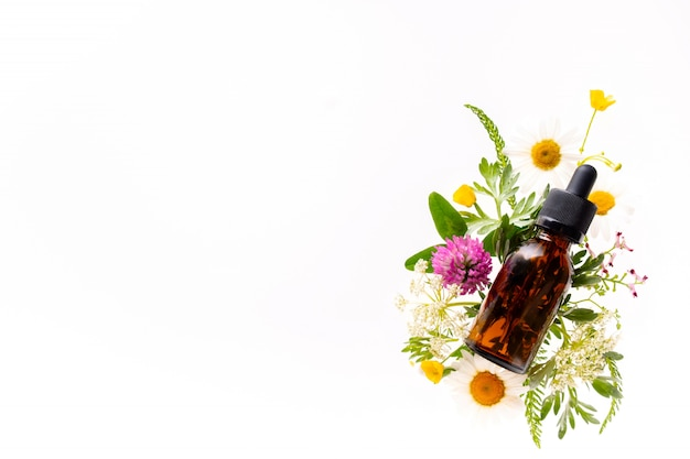 Wild flowers and medicine glass bottle on white