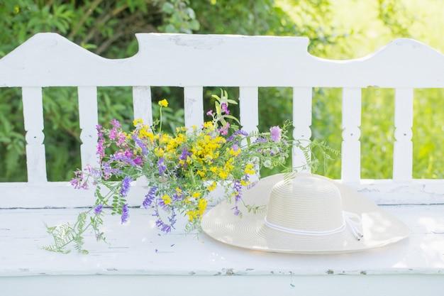 Полевые цветы на белой деревянной скамейке в летнем саду