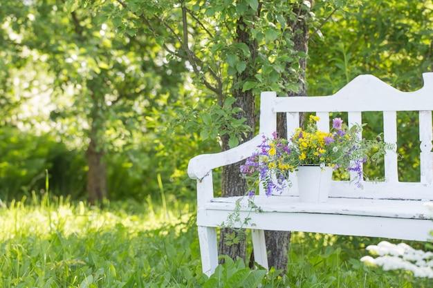 夏の庭の白い木製のベンチに野生の花