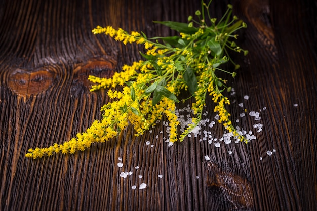 Wild flowers and salt on wooden table
