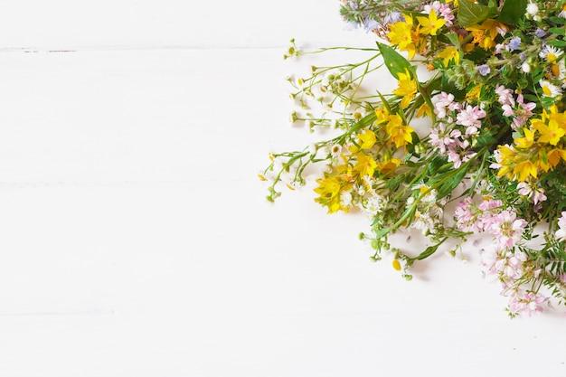Полевые цветы с соломенной шляпой на белом