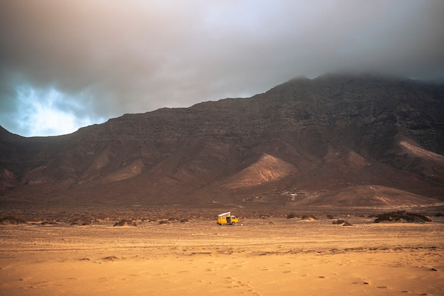 Wild and free lonely camping with old vintage scenic yellow van parked alone with beach in forehand and mountains with clouds in backgorund