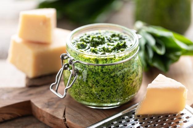 Песто из дикого лука-порея с оливковым маслом и сыром пармезан в стеклянной банке на деревянном столе. полезные свойства черемши. листья свежей черемши. по горизонтали