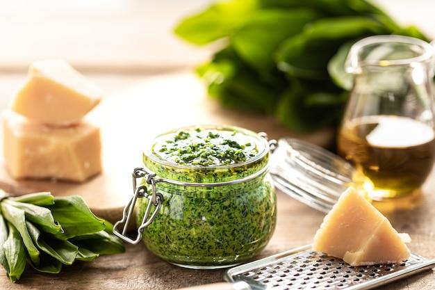 Песто из дикого лука-порея с оливковым маслом и сыром пармезан в стеклянной банке на деревянном столе. полезные свойства черемши. листья свежей черемши.