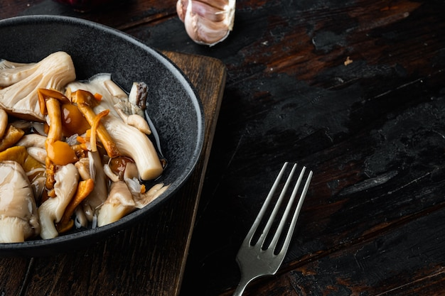 野生のキノコ食用キノコとヤマドリタケの瓶セット、古い暗い木製のテーブルの背景、テキストコピースペース用のスペース