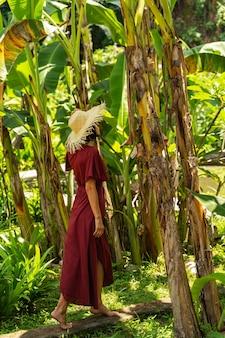 야생의 자연. 그녀의 모자를 만지고 밝은 녹색 열대 식물을 즐기면서 기대하는 놀라운 젊은 여성