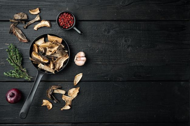주철 프라이팬에 있는 야생 유기농 말린 포르치니 버섯, 검은색 나무 테이블 배경, 위쪽 전망 플랫 레이, 텍스트 카피스페이스를 위한 공간