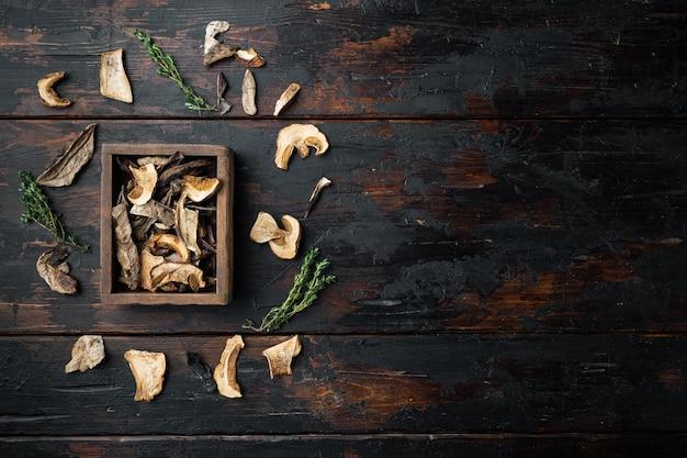 野生の有機乾燥ポルチーニ茸セット、古い暗い木製のテーブルの背景、上面図フラットレイ、テキストコピースペース用のスペース