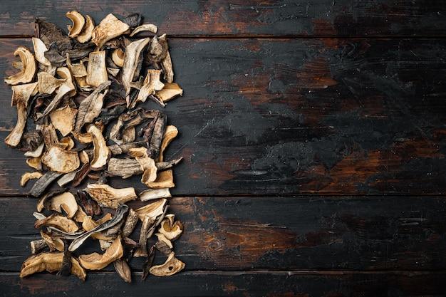 野生の有機乾燥ポルチーニ茸セット、古い暗い木製のテーブルの背景、上面図フラットレイ