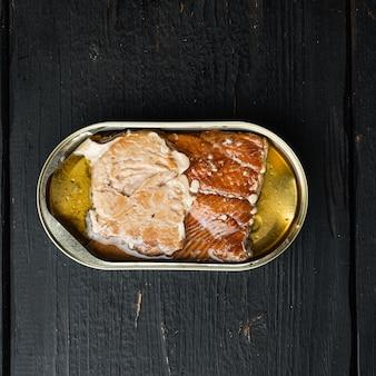 Набор консервов из копченой рыбы из дикого горбуши, в жестяной банке, на черном деревянном столе, плоская планировка, вид сверху, квадратный формат