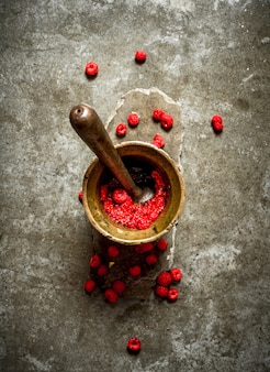 Wild raspberries in old mortar with pestle.