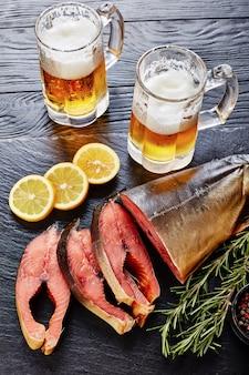 Дикий лосось нарезанный на стейки со свежим вспененным пивом в стеклянных чашках