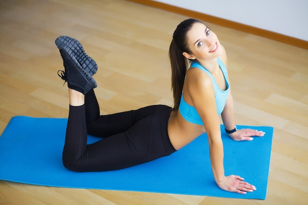 Молодая женщина, практикующая йогу, делает wild thing, flip-the-dog упражнение, поза camatkarasana, тренировка, ношение спортивной одежды, черные брюки и топ, крытая полная длина, серая стена в студии йоги