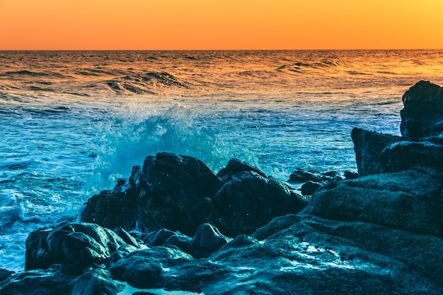 Wild waves splashing on rocks at sunset colorful twilight by the sea nature beauty concepts