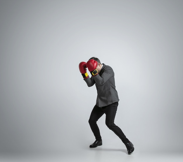 Wild and young. caucasian man in office clothes boxing with two red gloves on grey background