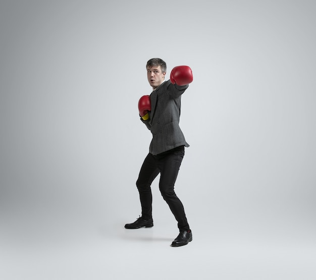 Wild and young. caucasian man in office clothes boxing with two red gloves on grey wall. businessman training in motion, action. unusual look for sportsman, activity. sport, healthy lifestyle.