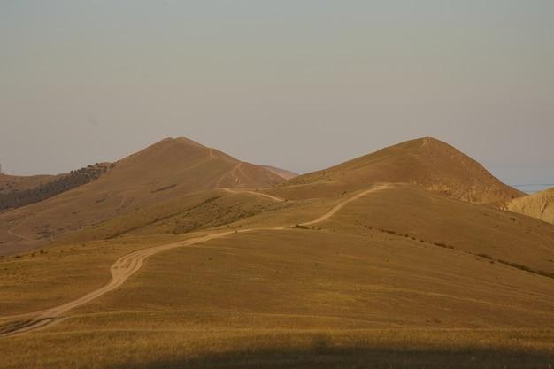 荒野、砂漠、風景、屋外、野生の自然の概念。 2つの高い丘の間の人けのないエリアを横切って走る田舎道。背景に青い海が現れる乾燥した茶色の高地