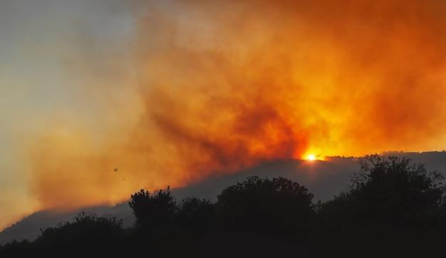 극적인 붉은 하늘과 무거운 연기와 함께 일몰 산 비탈에 산불