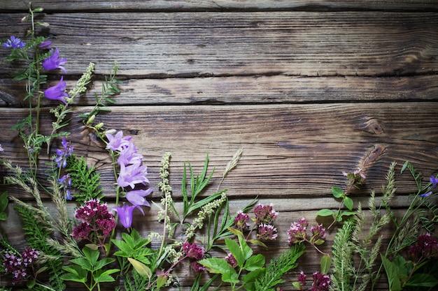 暗い古い木製の背景に野生の花