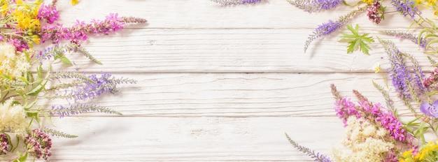白い木製の背景の野の花