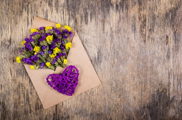 Wildflowers in paper envelope and wicker heart