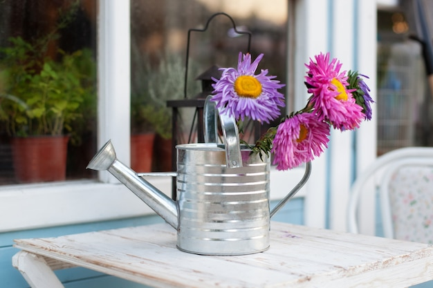 Wildflowers in watering cans on white table in garden. gardening tools, houseplants and flowers on terrace.