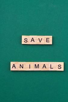 野生生物保護のスローガン。動物の概念を保存します。緑の背景に分離された文字と木製の立方体。