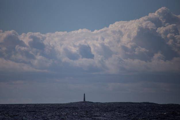 Valaam 자연 보호 구역의 야생 동물 - 신성한 섬. 멀리 등대가 있는 섬이 보입니다. 하늘에는 거대한 흰 구름이 있습니다. 텍스트를 위한 공간이 있습니다.