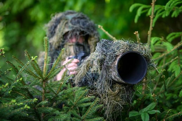 Фотограф дикой природы в летнем камуфляжном костюме гилли работает в дикой природе