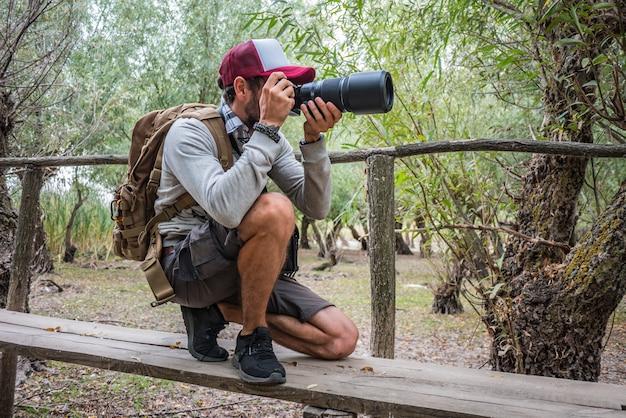 野生動物写真家が座って国立公園でカメラの焦点を合わせます