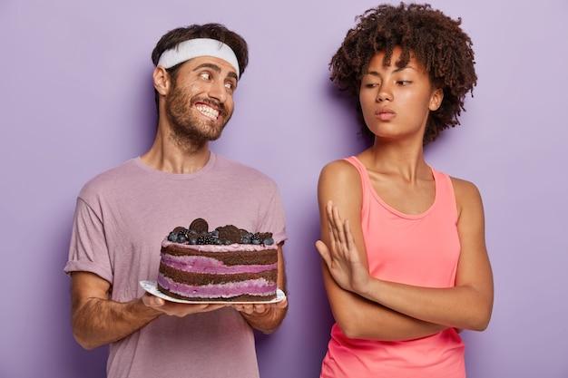 パワードダークスキンの女性はプレート上のおいしいケーキを消費することを拒否します