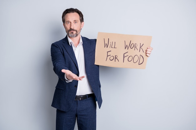 Will work for food. photo of dismissed mature guy financial crisis failure lost job hold carton placard spread hand street people asking human kindness wear suit isolated grey background