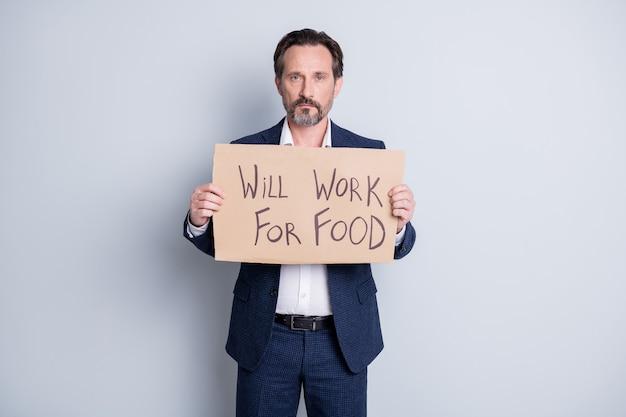 Буду работать за еду. фотография серьезного грустного бедного рабочего, уволенного парня, страдающего финансовым кризисом, потеряла работу, удерживайте плакат, ищите работу, чтобы обменяться едой, носите синий костюм, изолированный серый фон