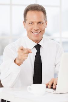 Ты присоединишься к моей команде? веселый зрелый мужчина в рубашке и галстуке, указывая на камеру и улыбаясь