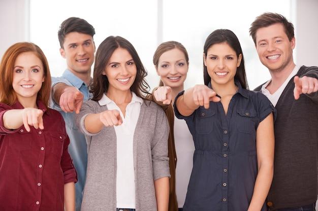 Вы присоединитесь к нашей команде? группа веселых молодых людей, стоящих рядом и указывающих на вас