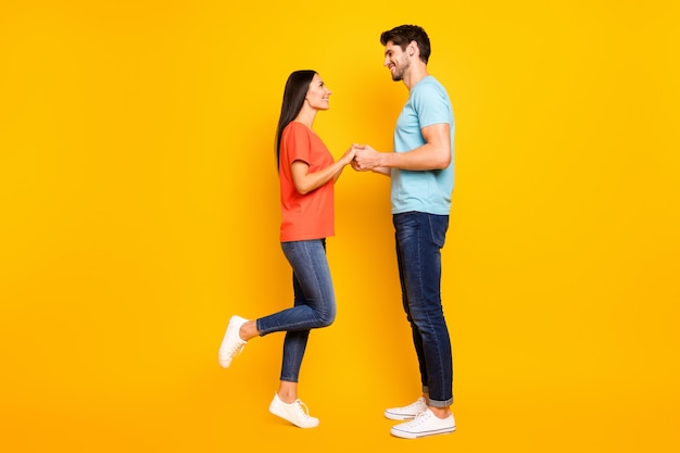 Will you marry me? full body photo of two cute people couple guy lady hold arms look eyes love declaration wear casual blue orange t-shirts jeans isolated yellow color wall