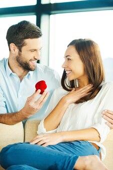 Ты выйдешь за меня замуж? красивый молодой человек делает предложение, даря обручальное кольцо своей девушке