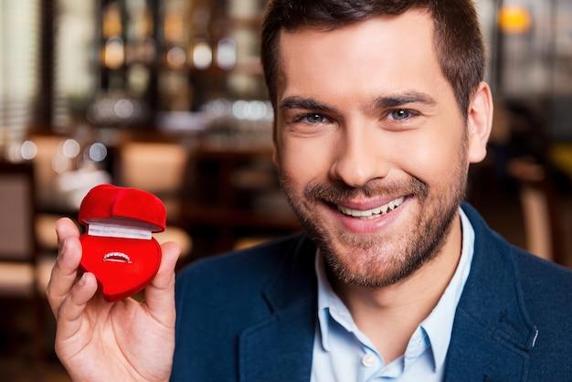 Ты выйдешь за меня? красивый молодой человек делает предложение, держа коробку с обручальным кольцом Premium Фотографии