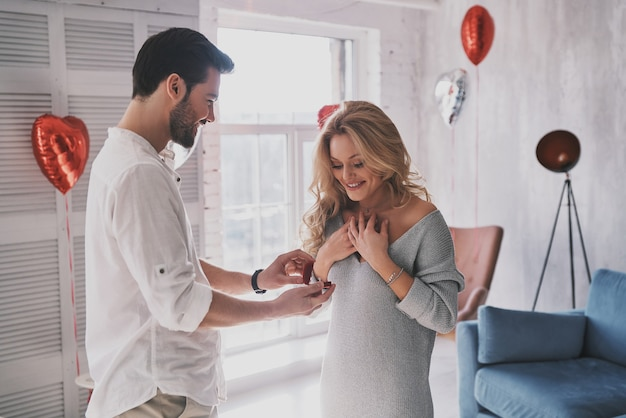 Ты выйдешь за меня? удивленная молодая женщина с улыбкой смотрит на обручальное кольцо, стоя в спальне, полной воздушных шаров