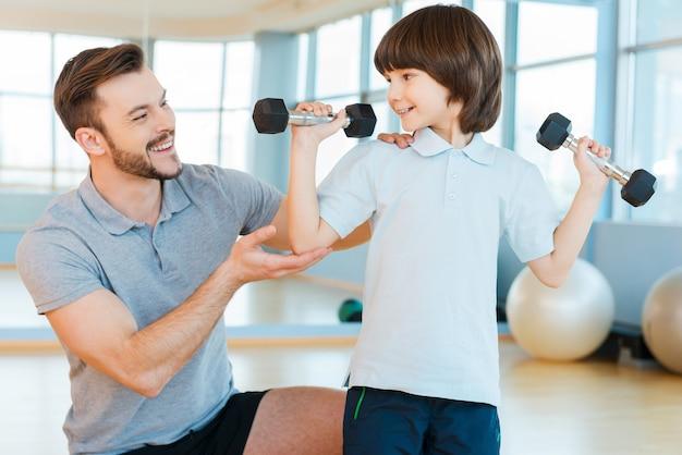 強くて健康になりたい。両方がヘルスクラブに立っている間、ウエイトエクササイズで彼の太陽を助けている幸せな父