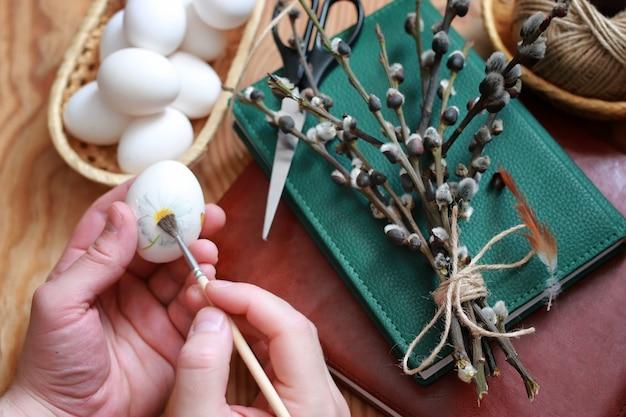 木製の背景に柳と卵