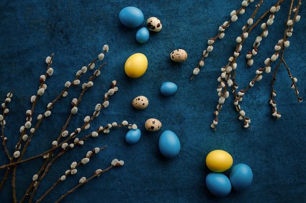 青い布の背景に柳の枝とイースターの卵