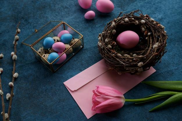 柳の枝とチューリップ、イースターエッグ、装飾的なギフトボックスと青い布の背景に巣